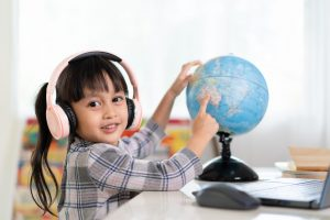 Asian beautiful little student girl is smiling and pointing on bilingual globe model for her online lesson, concept of learn from home and homeschooling for child education.